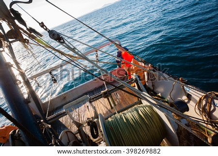 Fishermen standing at the stern of small fishing vessel. Sea of Japan.