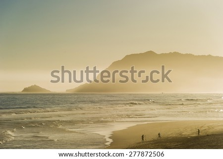 Fishermen with rods on a sandy beach during sunset. - stock photo