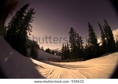 Fisheye shot of a skiing slope in the alps. Warm tones are intentional to create mood. - stock photo