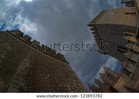 Fisheye view of towers of Almodovar del Rio medieval castle against the cloudy sky - stock photo