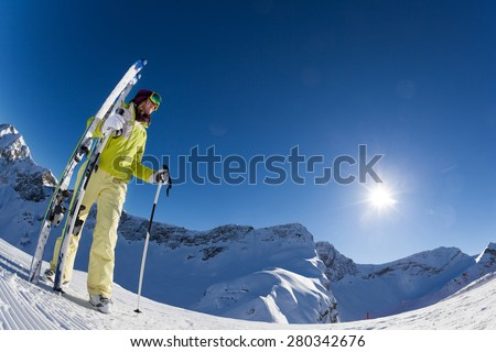 Fisheye view of woman standing and holding ski and ski poles during sunny winter day on Krasnaya polyana ski resort and Caucasus mountains in Sochi, Russia - stock photo