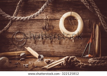 Fishing accessories spread out on a shelf in an old barn. - stock photo