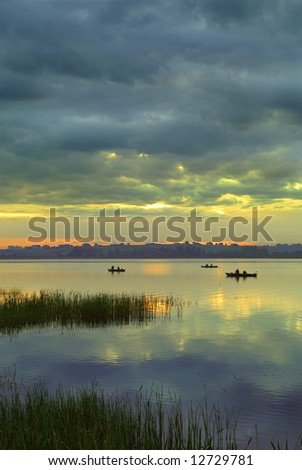Fishing at dawn under an beautiful sunrise - stock photo