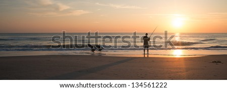 Fishing at Sunrise in Melbourne Beach, Florida. - stock photo