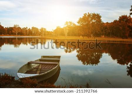 Fishing boat and autumn landscape - stock photo