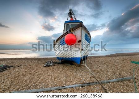 Fishing boat at dawn on a shingle beach - stock photo