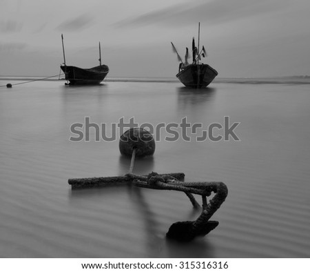 Fishing boat at the beach during sunset in black and white