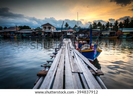 fishing boat at the pier in thai fishing village - stock photo