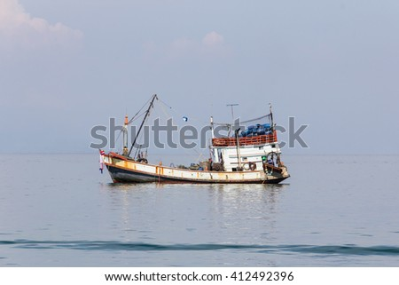 Fishing boat float on the sea with calmness - stock photo