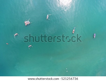 Fishing boat floating in the sea. The beautiful bright blue water in a clear day.The sun shines the light reflected off the surface.Top view.