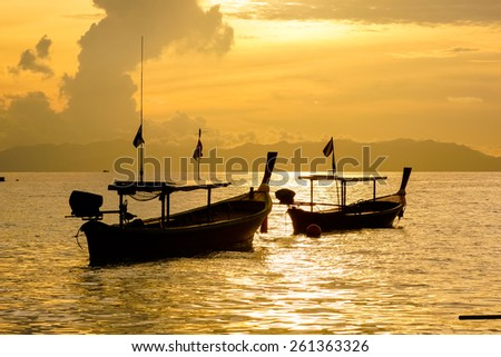 Fishing boat floating on the sea at dawn. - stock photo