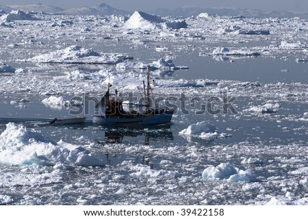 Fishing boat going through the icy waters of Ilulissat, Greenland - stock photo