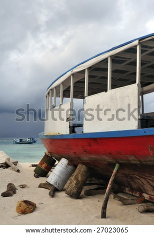 Fishing boat in dry-dock with storm in background, Maldives