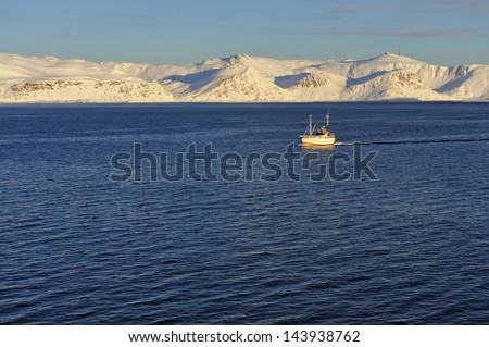 fishing boat in front of snow covered mountains - stock photo