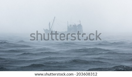 Fishing boat in rain strom , Gulf of Thailand. - stock photo