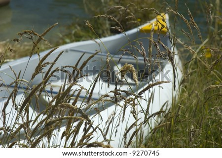 Fishing boat in the grass by the water. Summer concept