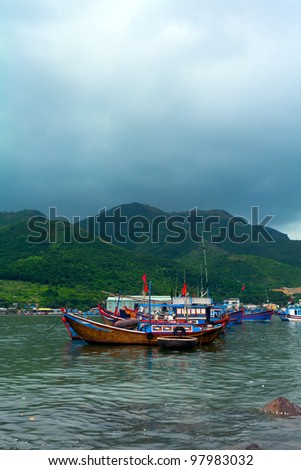 Fishing boat in the sea among mountains and clouds - stock photo