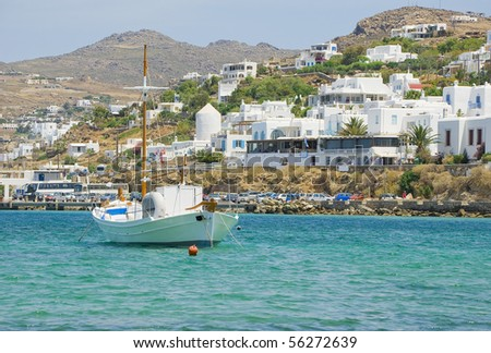 Fishing boat in the sea anchor on the background of the island of Mykonos with its white houses and windmills...