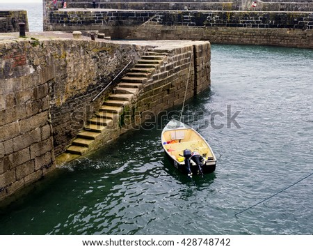 Fishing boat moored in tiny harbour   - stock photo