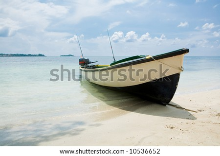 Fishing boat on a beach with water and blue skies - stock photo