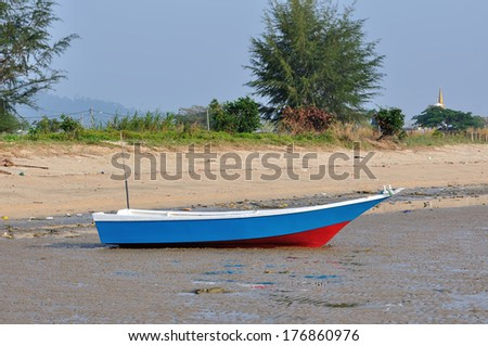 Fishing boat on the beach in the morning - stock photo