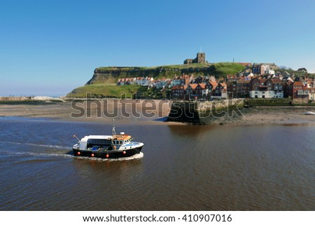 Fishing boat returns to harbour sailing up River Esk, Whitby, North Yorkshire. - stock photo