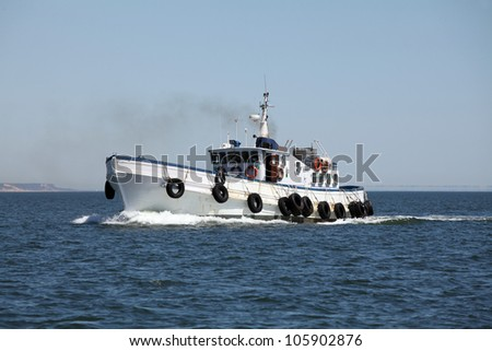 Fishing boat, sailing out to the ocean at the afternoon - stock photo