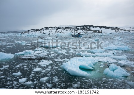 Fishing boat sailing through the icy waters of Ilulissat, Greenland - stock photo
