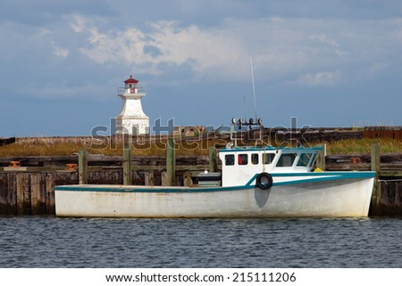 Fishing boat with lighthouse. - stock photo