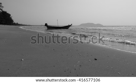 Fishing boat with no fisherman on a wide sand beach
