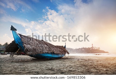 Fishing boat with palm tree leaves on the beach in the morning at lighthouse background in Kovalam, Kerala, India   - stock photo