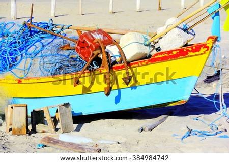 Fishing boat. Wooden fishing boat anchored on beach sand full of fishing stuff      - stock photo