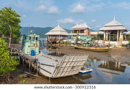 fishing boats and ferry moored on the coast in Fishing Village of the Koh Chang island,Thailand . - stock photo