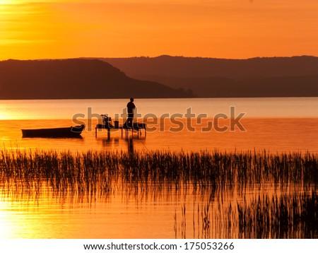 fishing boats and fisherman in the sunset at Lake Balaton - stock photo