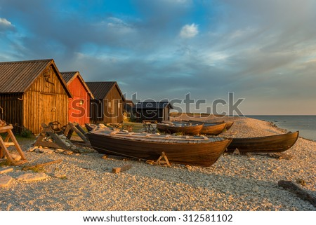 Fishing boats and fishing cabins on the stony beach of Faro, Sweden, in the light of the sunrise - stock photo