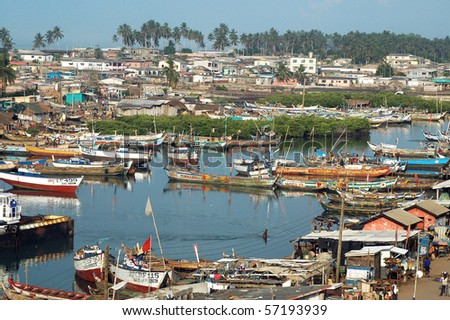 Fishing boats and houses at Elmina harbour - stock photo
