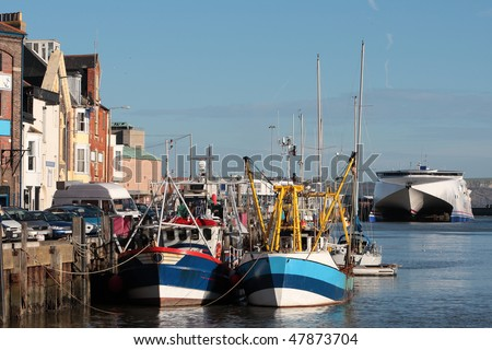 Fishing boats and trawlers in Weymouth harbour in Dorset, home of the 2012 Olympic Sea Games - stock photo