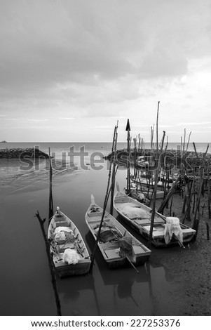 Fishing boats at muddy beach in black and white