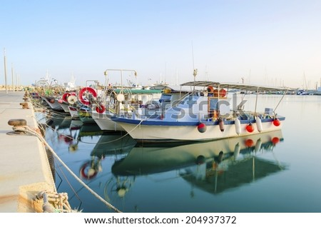 Fishing boats docked at the Limassol old port in Cyprus,next to the Marina part of the ports authority.A view of the harbor, the mediterranean sea, the water, boat and fish nets and fishing equipment. - stock photo