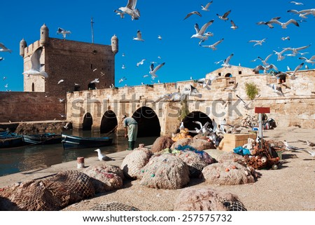 Fishing boats, gear and catch on background of Castelo Real of Mogador. Essaouira, Morocco - stock photo