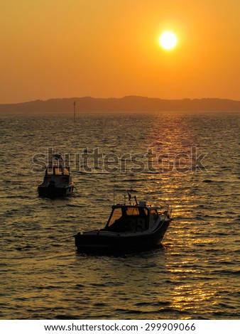 Fishing boats in a bay at sunset