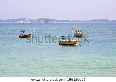 Fishing boats in beautiful ocean near coastline of Sri Lanka, Ceylon. Horizontal image