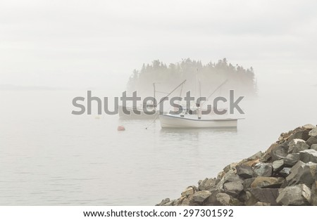 Fishing boats moored in Lubec Narrows near Bay of Fundy of Coastal Maine with thick fog beginning to lift. - stock photo