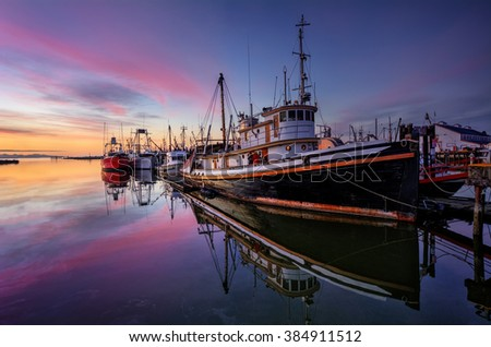 Fishing boats moored on the river creating reflections on the clear water, pastel coloured sunset on the horizon - stock photo