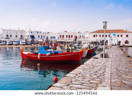 Fishing boats near the pier in the old port of Mykonos and the famous church. Greece - stock photo
