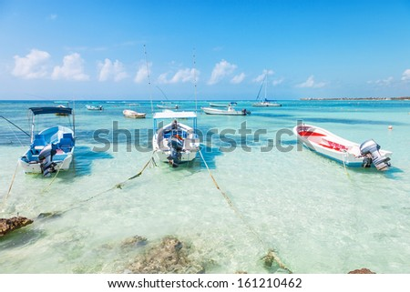 fishing boats on a Caribbean beach with transparent water - stock photo