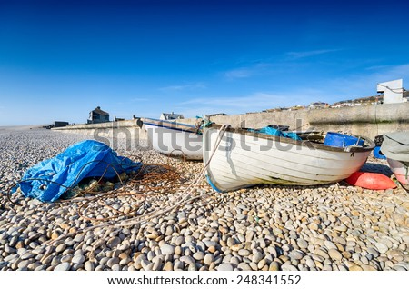 Fishing boats on a pebble beach at Chesil Cove on the Portland side of Chesil Beach in Dorset - stock photo
