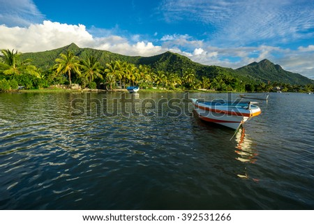 Fishing boats on the background of incredible golden sunset, clouds and high mountains. Mauritius Island, Indian Ocean