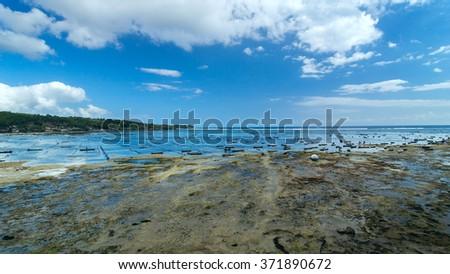 Fishing boats on the coastline of island Bali in Indonesia. Seaside Plantation shellfish. - stock photo