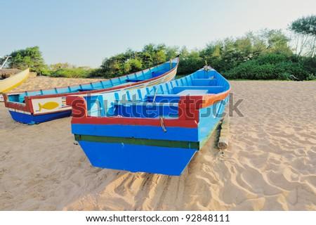 Fishing boats on the sandy beach in Goa - stock photo